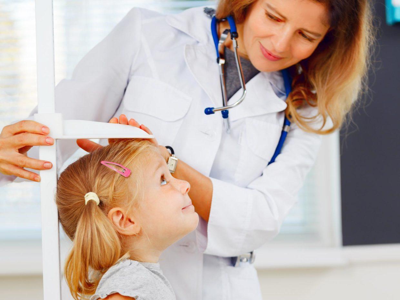 la pediatra misura l'altezza di una bambina