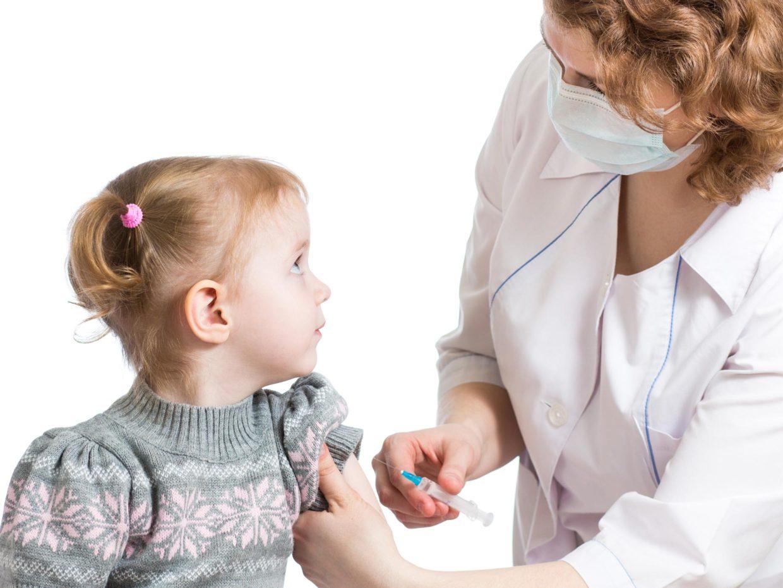 ragazzina si guarda con il medico che tiene in mano la siringa