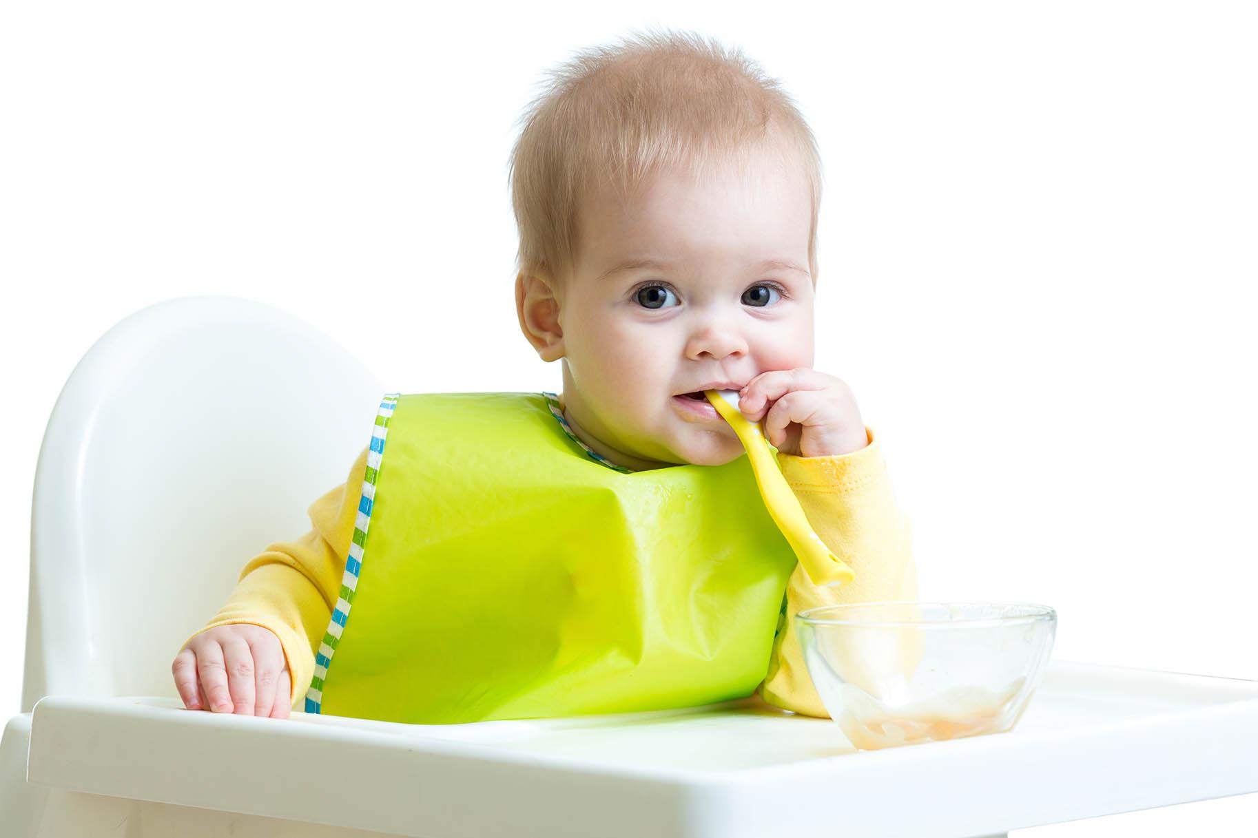 bambino sul seggiolone con cucchiaino in bocca