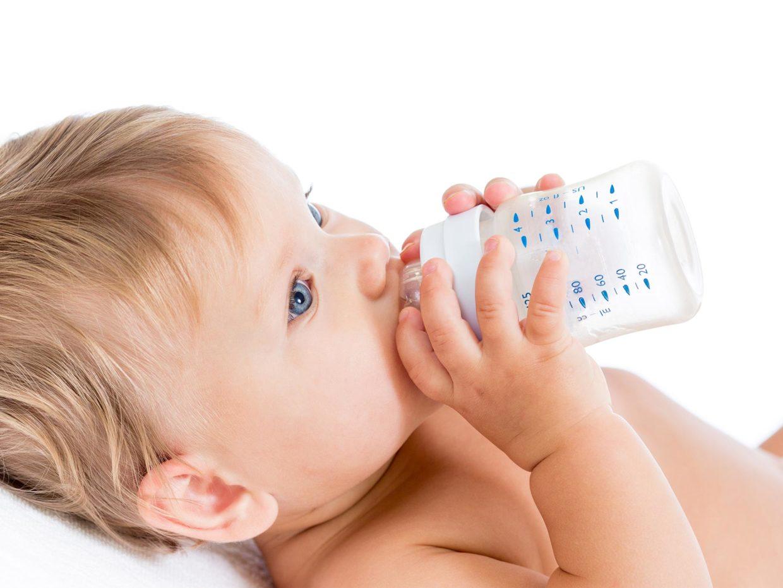 bambino beve il latte dal biberon