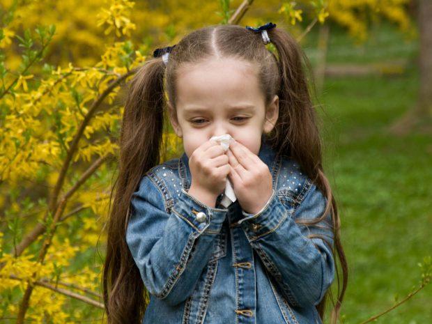 bambina con lunghi capelli si soffia il naso in un campo di fiori