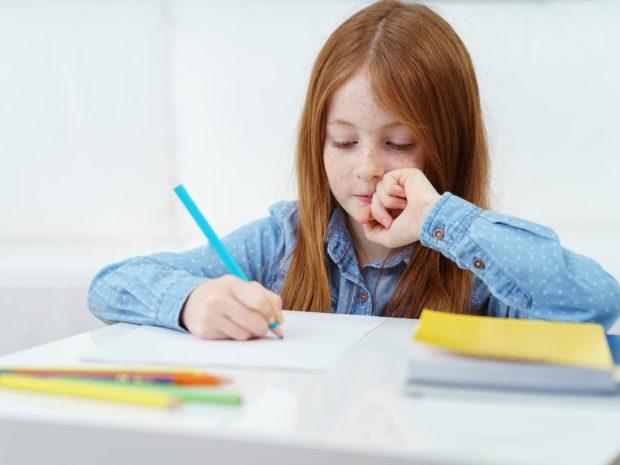 bambina con i capelli rossi impegnata a fare i compiti