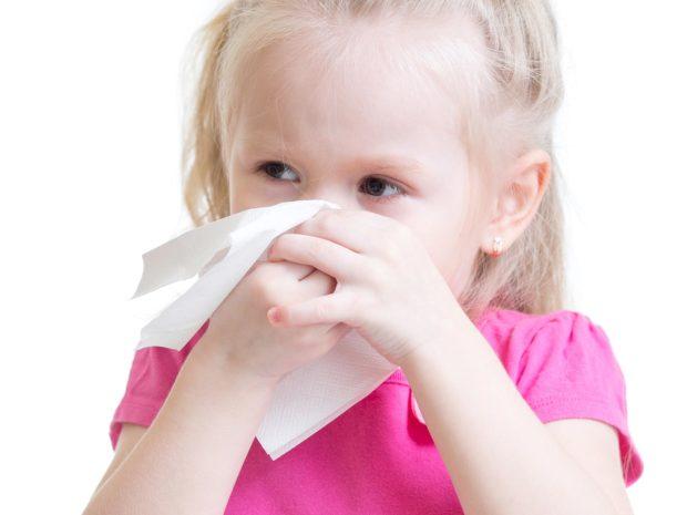 bambina bionda si soffia il naso