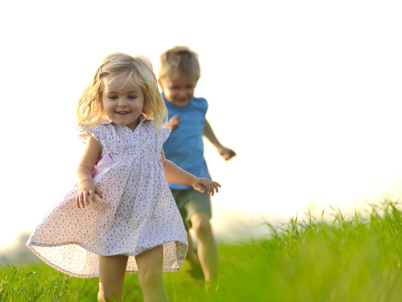 due bambini felici corrono in un prato