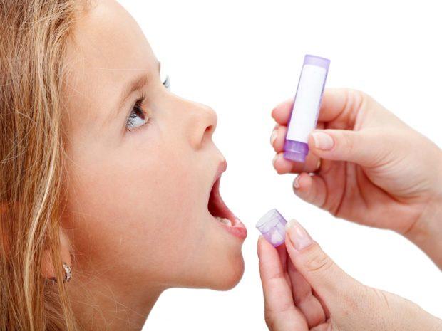 bambina a cui viene somministrato un medicinale in pillole