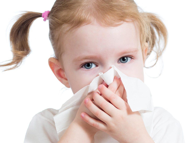 bambina con le codine si soffia il naso