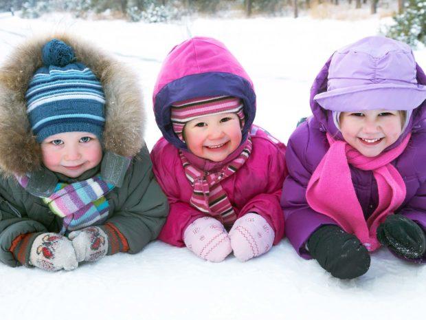 tre bambini sorridenti distesi sulla neve