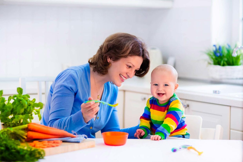 mamma dà da mangiare al figlio piccolo con il cucchiaino