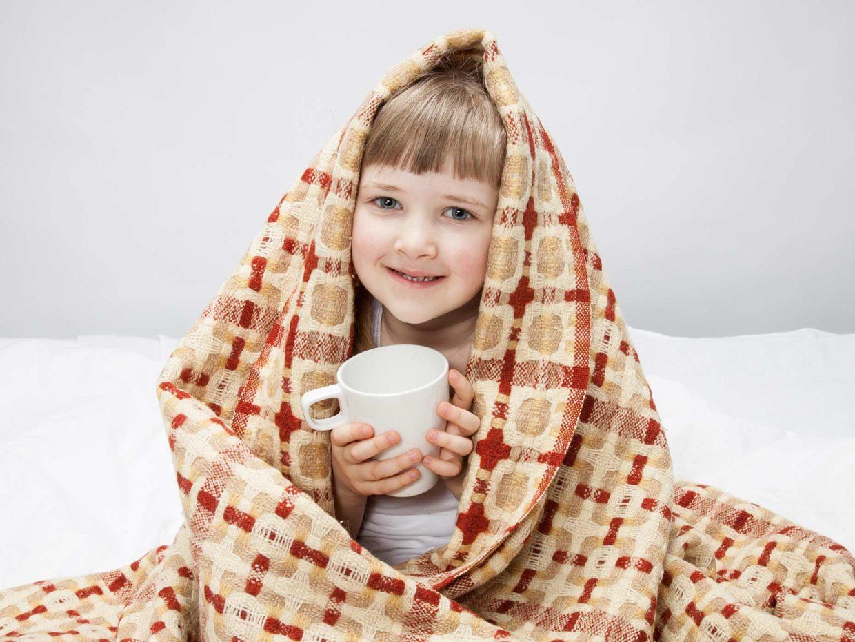 bambina sotto le coperte con tazza in mano