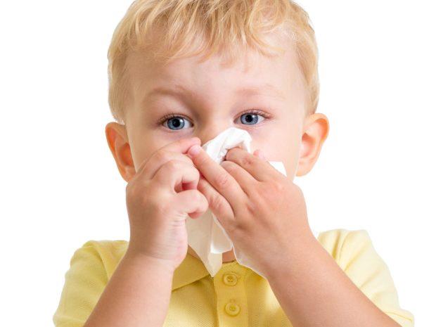 bambino biondo con maglietta gialla si soffia il naso
