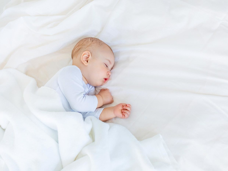 neonato dorme tranquillo sul letto
