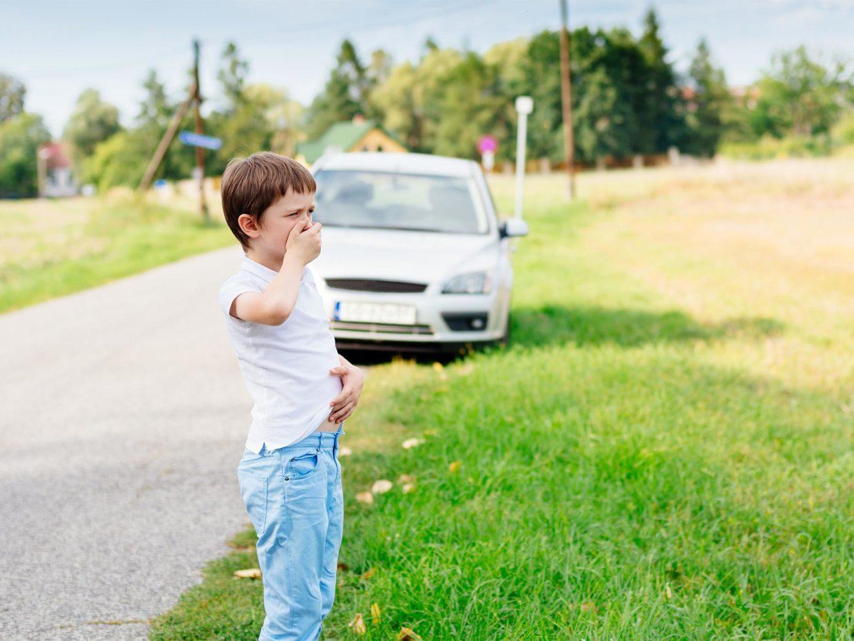 macchina accostata sul ciglio della strada accanto bambino che soffre di nausea