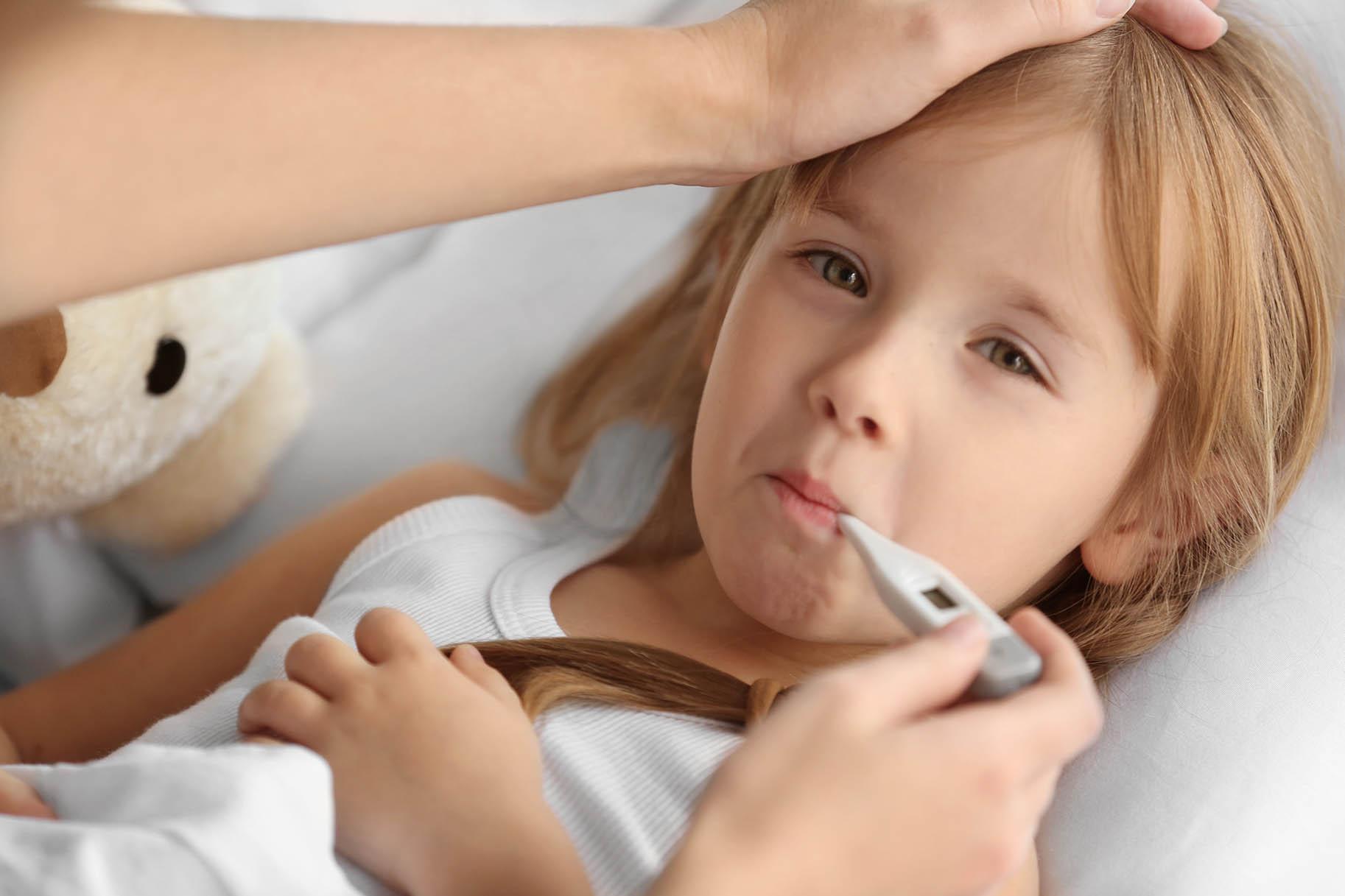 bambina a letto con l'influenza si misura la temperatura