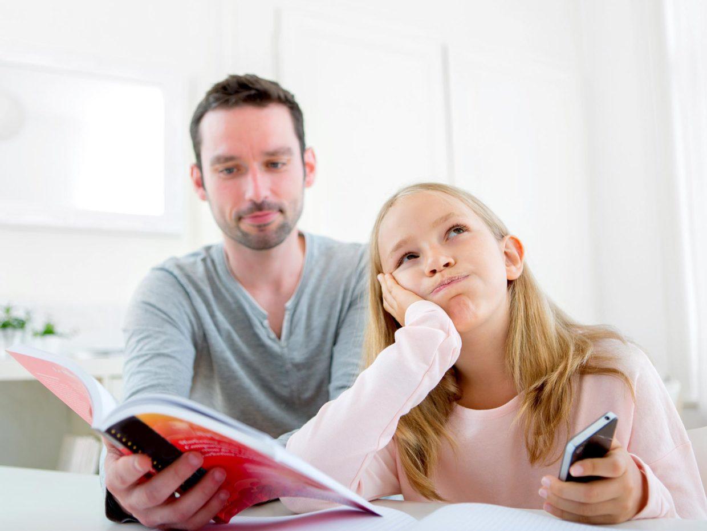 bambina bionda sbuffa con accanto il papà con un quaderno in mano