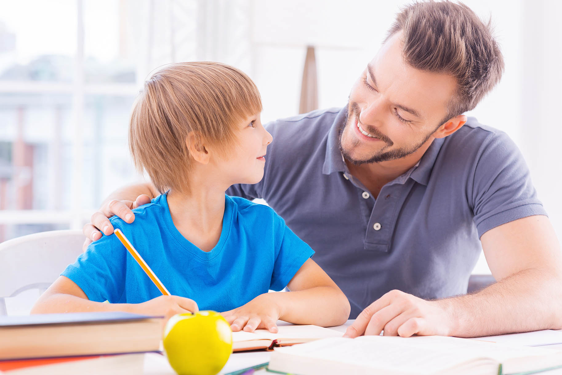 papà aiuta bambino a svolgere i compiti