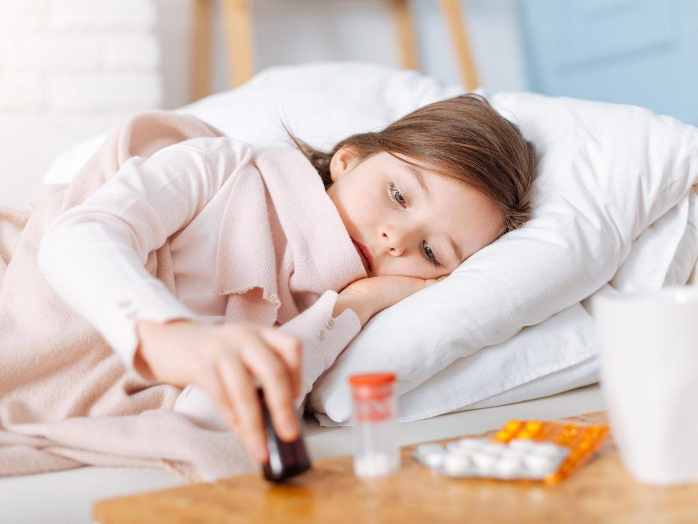 bambina malata a letto con accanto i medicinali