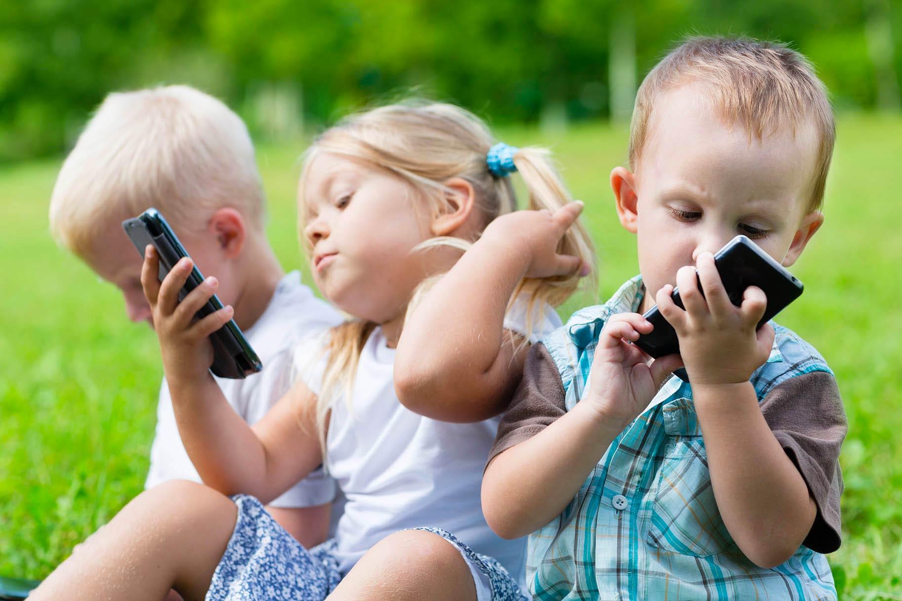 tre bambini piccoli usano lo smartphone