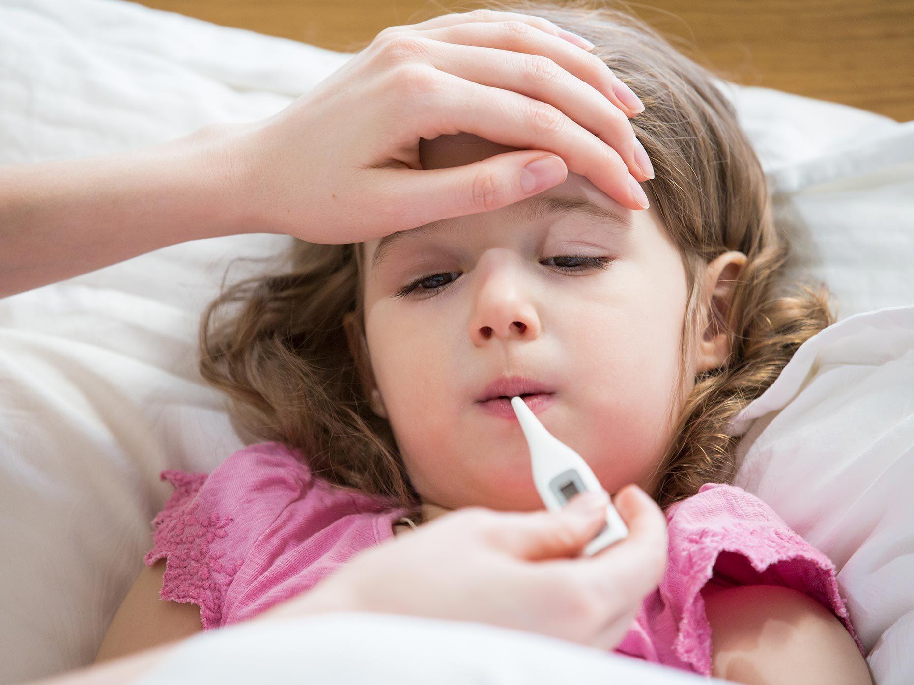 bambina a letto misura la febbre con il termometro