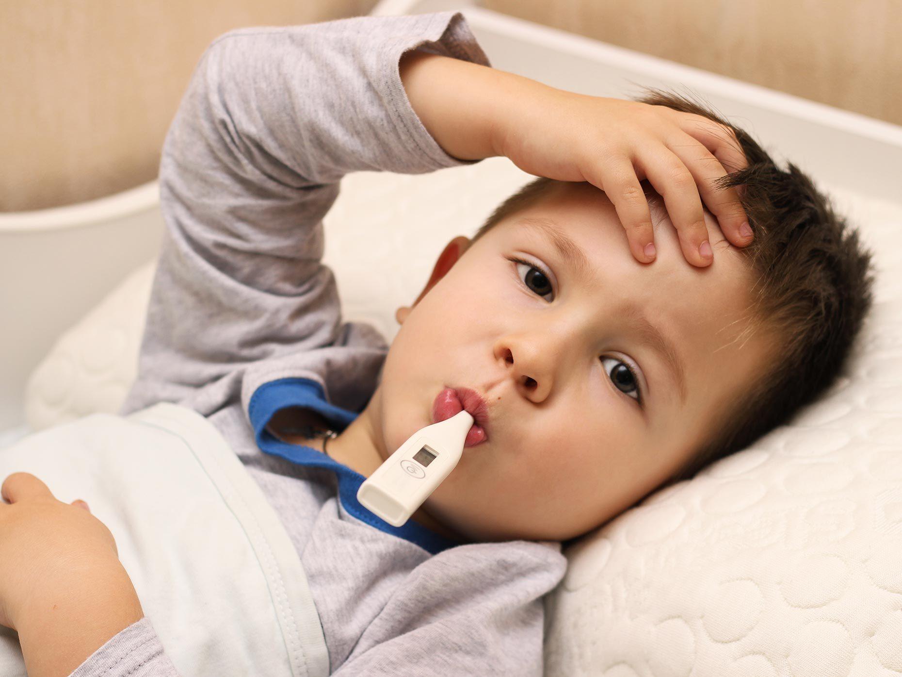 bambino con termometro in bocca si tocca la fronte
