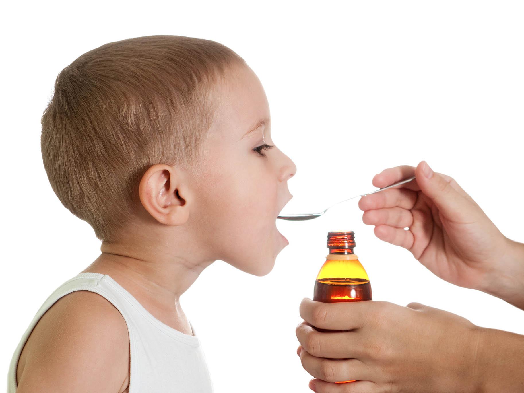 adulto porge un cucchiaino di sciroppo al bambino