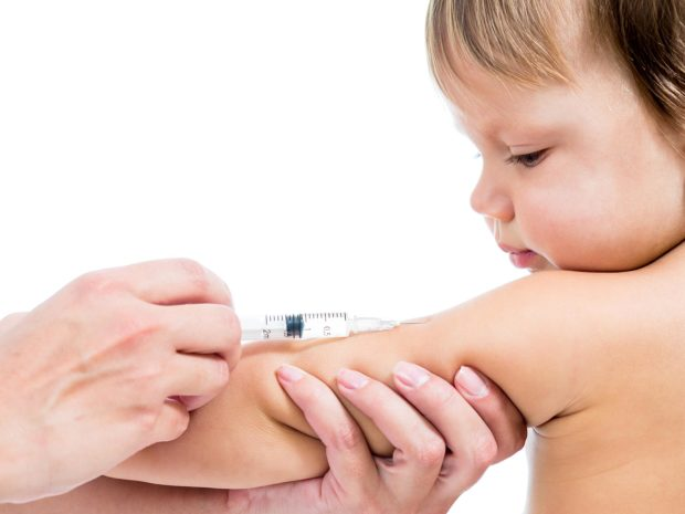 bambino guarda mentre viene vaccinato al braccio