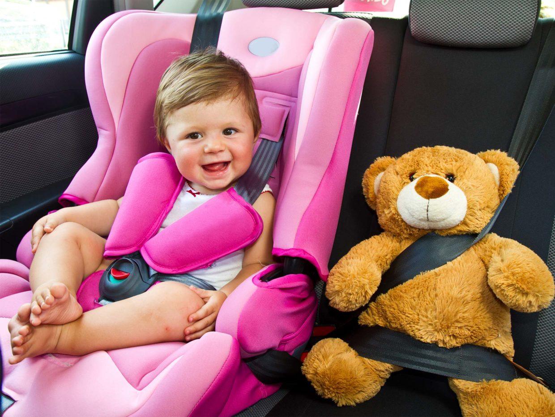 bambino felice sul seggiolino auto con il suo orsacchiotto di peluche