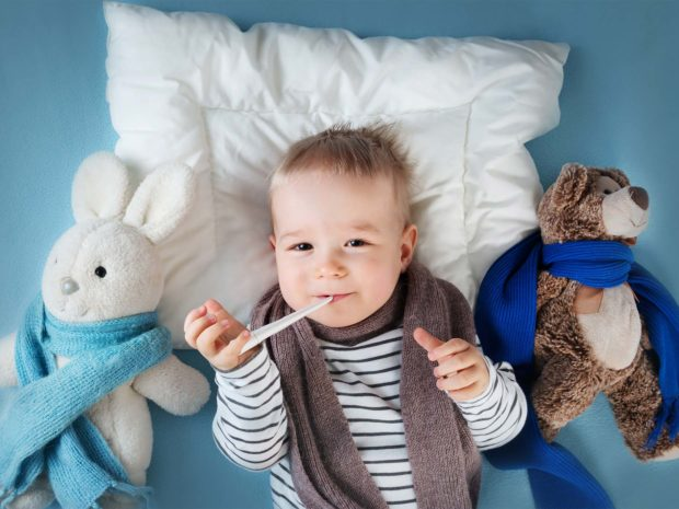 bambino disteso a letto con termometro alla bocca