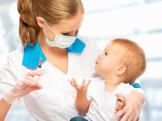 pediatra con in mano una siringa tiene in braccio un neonato