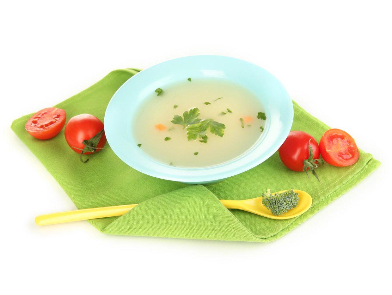 piatto di brodo vegetale con cucchiaio a fianco