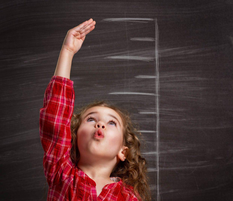 bambina misura la sua altezza grazie ad una scala metrica disegnata sulla lavagna