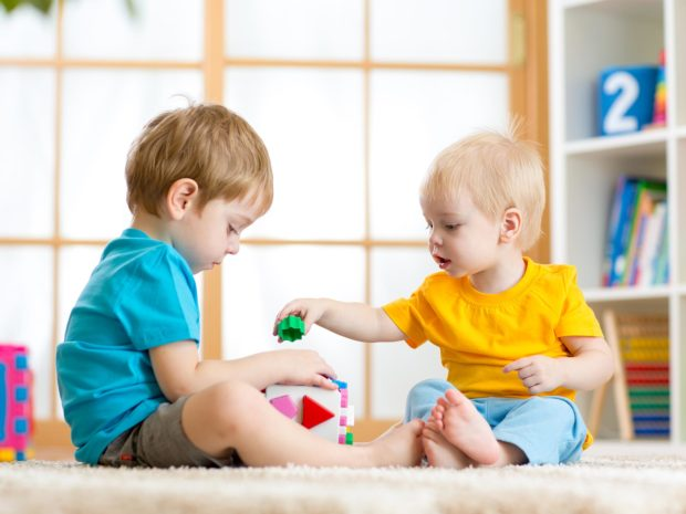 due bambini giocano con i mattoncini colorati sul pavimento di casa