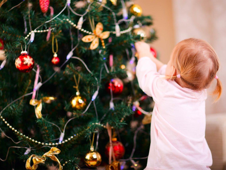 bambina piccola decora albero di natale