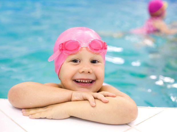 bambina appoggiata al bordo della piscina con cuffietka rosa