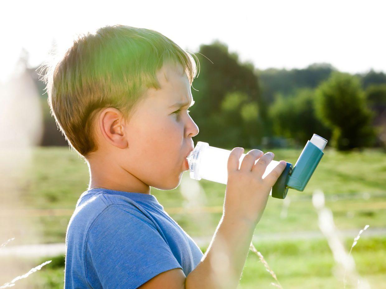 bambino in mezzo al prato utilizza distanziatore per inalatore spray