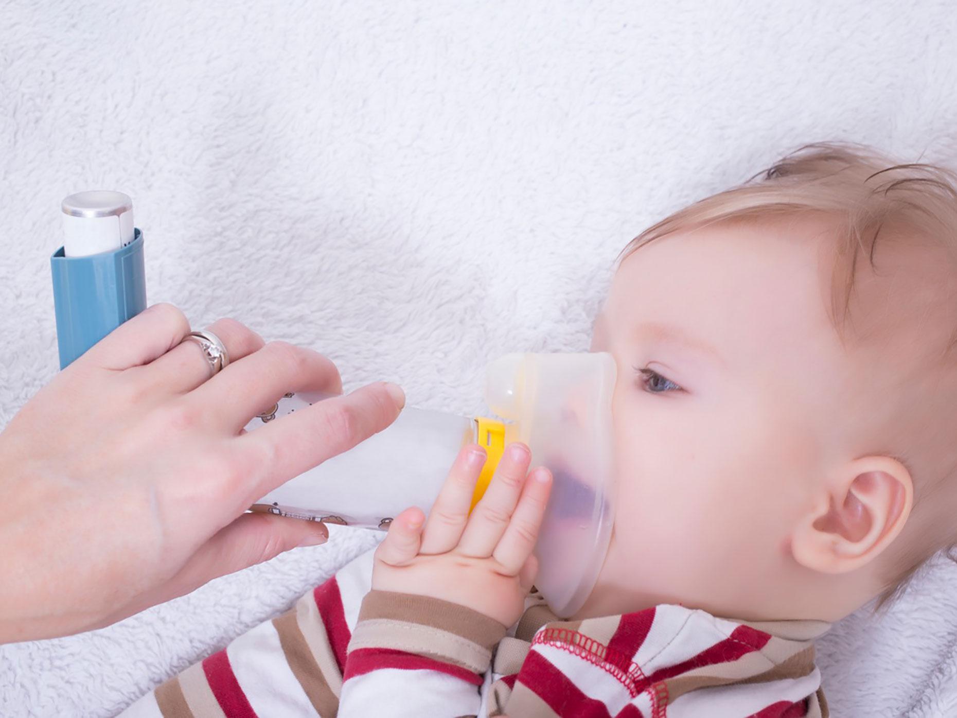 neonato utilizza con aiuto della madre distanziatore per inalatore spray