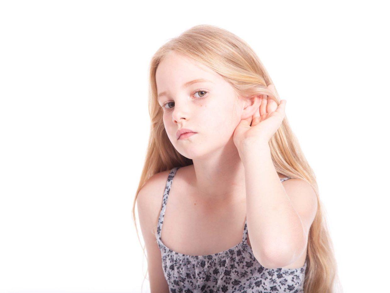 bambina bionda avvicina la mano all'orecchio per ascoltare
