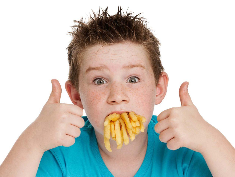 bambino con la bocca piena di cibo spazzatura