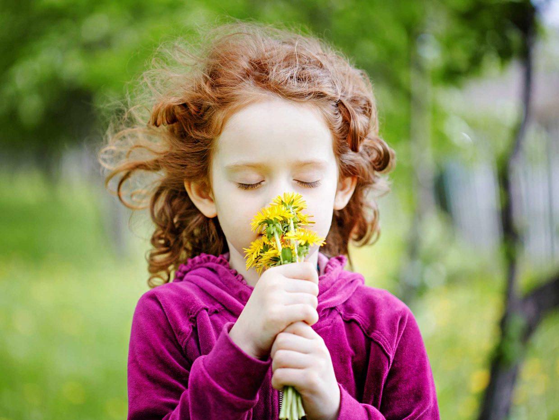 bambina con i capelli rossi annusa mazzo di margherite gialle