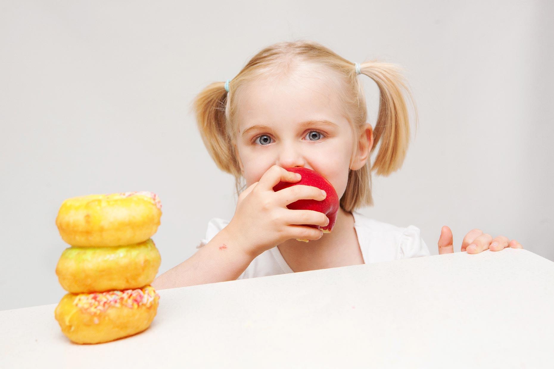 bambina mangia una mela e non le ciambelle