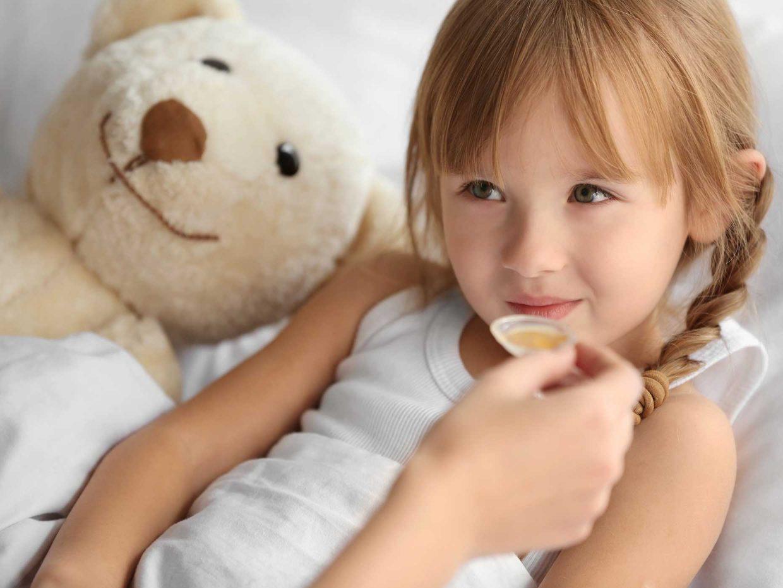 bambina malata a letto viene imboccata con il cucchiaino