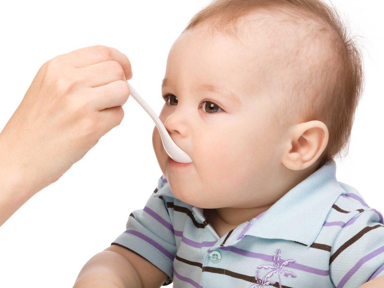 bambino imboccato dal genitore con il cucchiaino