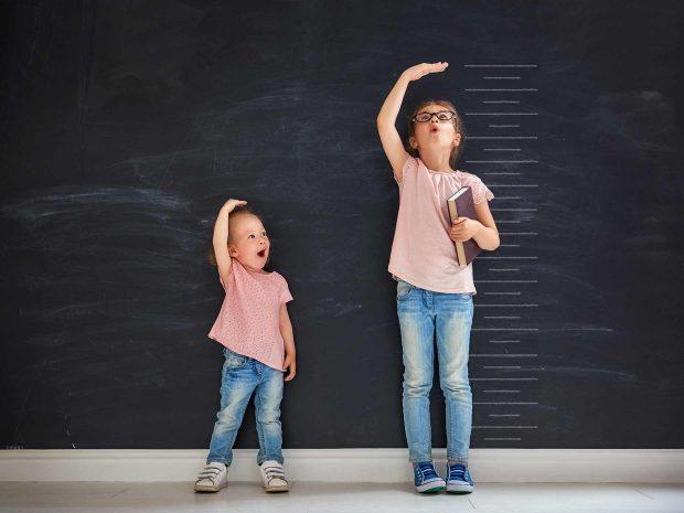 Fratello_e_sorella_si_misurano_davanti_a_una_lavagna