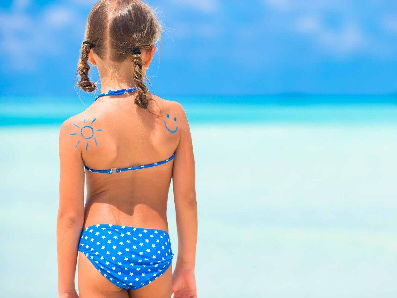bambina di spalle in costume con dei disegni, fatti con la crema solare, sulle spalle