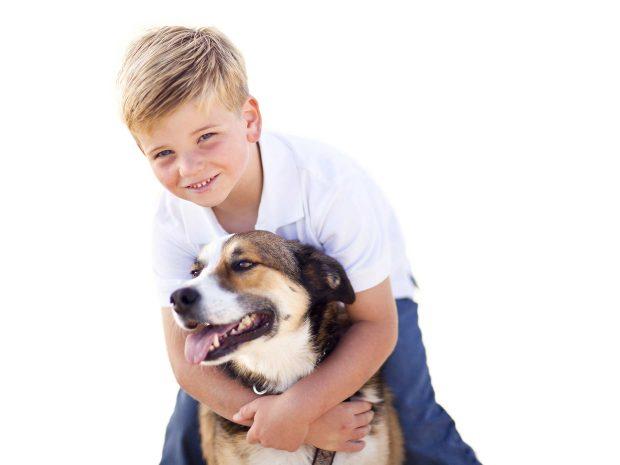 bambino biondo abbraccia da dietro cane di grossa taglia