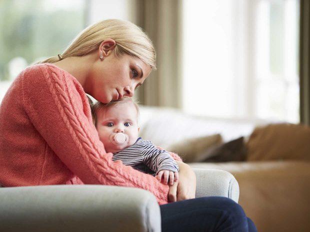 mamma triste abbraccia neonato seduta sul divano