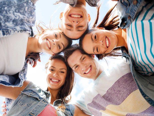ragazzi adolescenti ripresi dal basso sorridono abbracciandosi