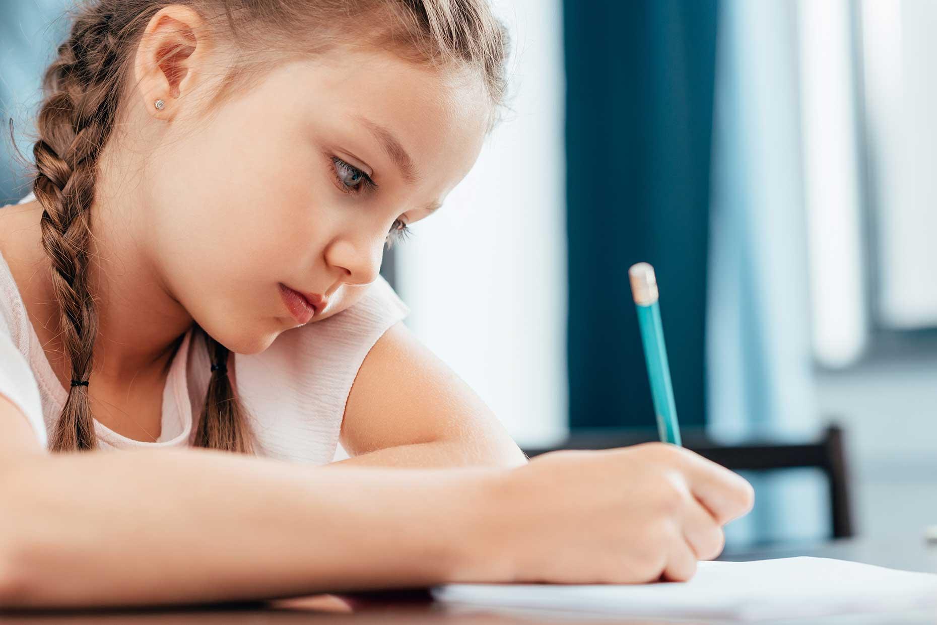 bambina con le trecce concentrata scrive con la matita