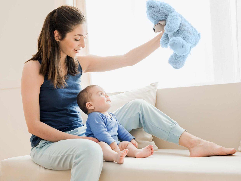 mamma tiene in alto orsetto di peluche azzurro mentre il bambino lo osserva
