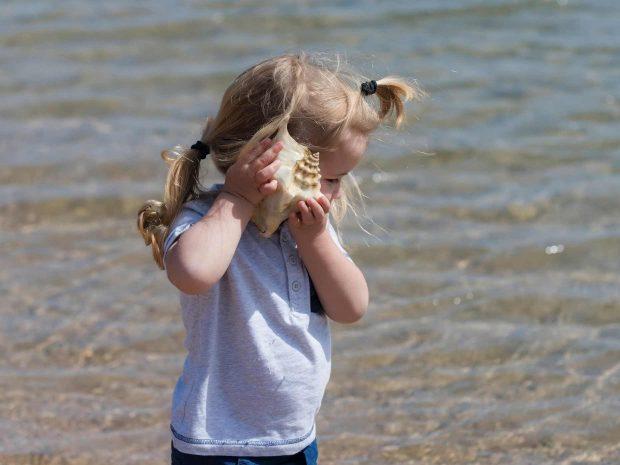bambina al mare ascolta i suoni prodotti da una conchiglia di mare