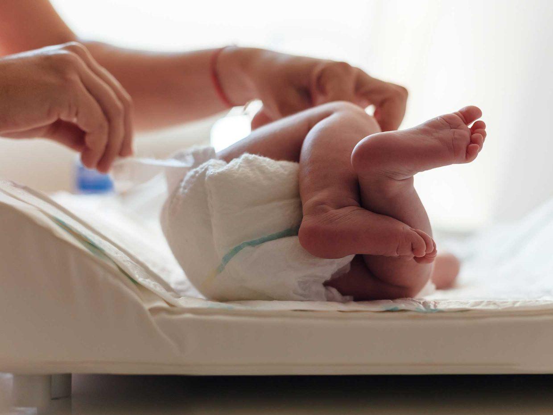 primo piano dei piedi di un neonato disteso su un fasciatoio